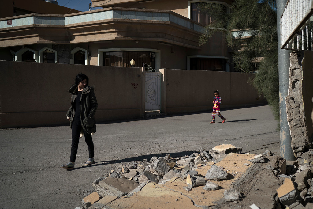 . Girls walk past a damaged house after an earthquake, in the city of Darbandikhan, northern Iraq, Monday, Nov. 13, 2017. A powerful 7.3 magnitude earthquake near the Iraq-Iran border has killed over 350 people across both countries, sent residents fleeing their homes into the night and was felt as far away as the Mediterranean coast. (AP Photo/Felipe Dana)