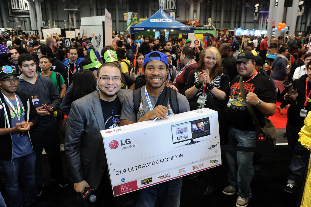 . Irvin Chase, right, of New York, celebrates after winning LG\'s new UltraWide monitor at a gaming tournament at New York Comic Con, taking place at the Jacob K. Javits Center, Friday, Oct. 11, 2013.  (Photo by Diane Bondareff/Invision for LG/AP Images)