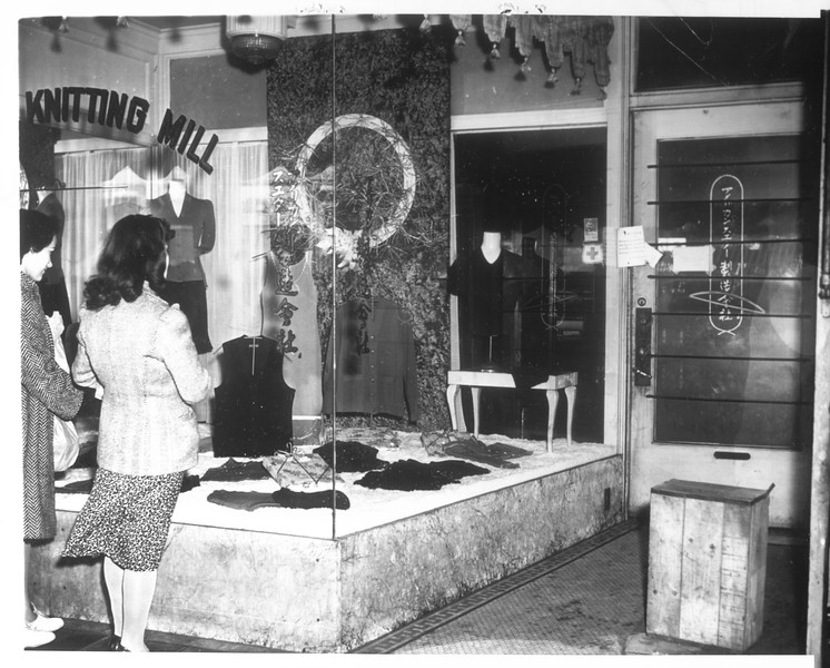 """""""Little Tokyo -- American Knitting Mill store, 244 East 1st Street.  Elizabeth Gatliff and Jennie Martinez of 112 North Glass Street look on sadly in window.""""--caption on photograph"""