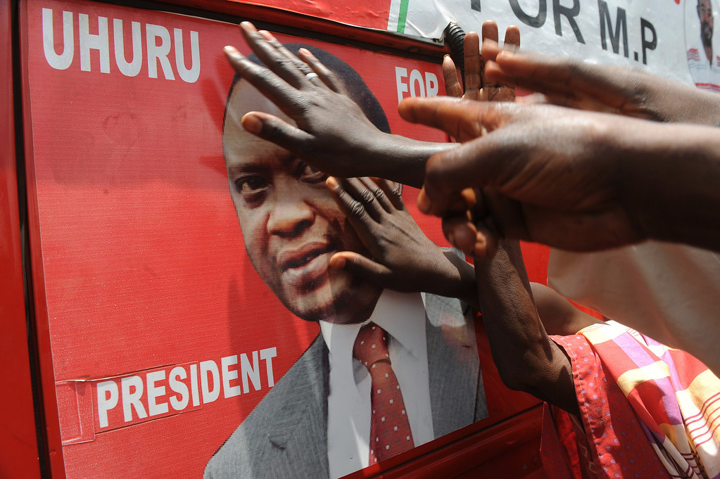 . Supporters of Kenyan presidential candidate Uhuru Kenyatta touch his picture on an election poster as they celebrate upon learning of his victory in Kenya\'s national elections on March 9, 2013 in Kiambu, north of Nairobi.  AFP PHOTO / SIMON MAINA