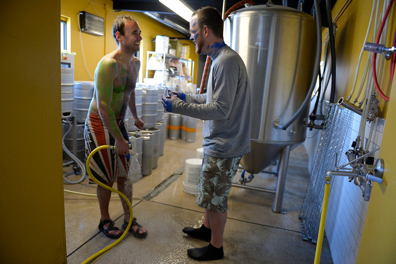 . Denver Beer Co. brewers (l-r) Patrick Crawford and Nick Bruno hose off with warm water after taking a plunge in the South Platte River at Confluence Park in Denver, CO February 06, 2014. (Photo By Craig F. Walker / The Denver Post)