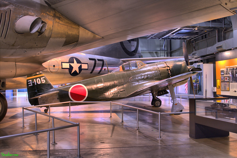 """National Museum of the United States Air Force, Dayton, Ohio,   04/12/2019  Mitsubishi A6M2 """"Zero""""  51553 The Museum  provided a partially restored airframe and a  second airframe that was recovered from the South Pacific  Islands several years ago. The aircraft was restored as  accurately as possible using factory drawings, photo research  and written documentation.   © Pacific Wrecks - A6M2 Model 21 Zero Manufacture Number 51553 Tail 313 Source: https://www.pacificwrecks.com/aircraft/a6m2/51553.html  This work is licensed under a Creative Commons Attribution- NonCommercial 4.0 International License."""