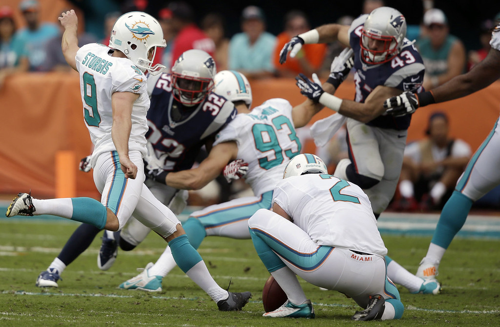 . Miami Dolphins kicker Caleb Sturgis (9) kicks a field goal during the second half of an NFL football game against the New England Patriots, Sunday, Dec. 15, 2013, in Miami Gardens, Fla. Miami Dolphins punter Brandon Fields (2) holds. (AP Photo/Lynne Sladky)