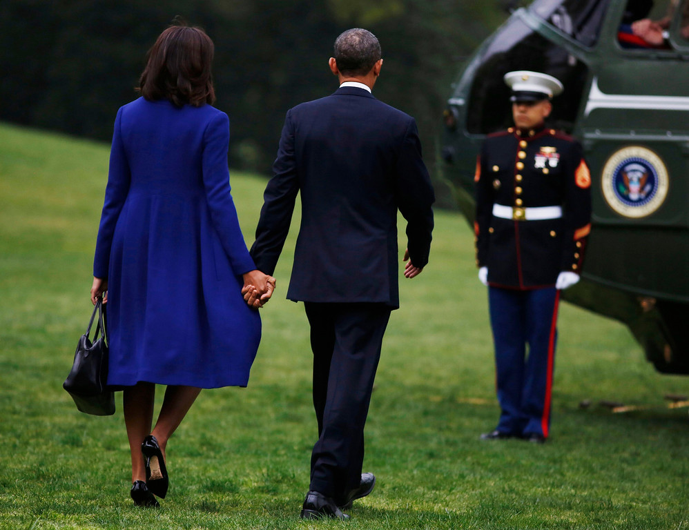 . U.S. President Barack Obama and first lady Michelle Obama walk towards Marine One before they depart the White House in Washington, on their way to a memorial service in Boston for victims of the bomb explosions at the finish line of the Boston Marathon on Monday, April 18, 2013. REUTERS/Larry Downing