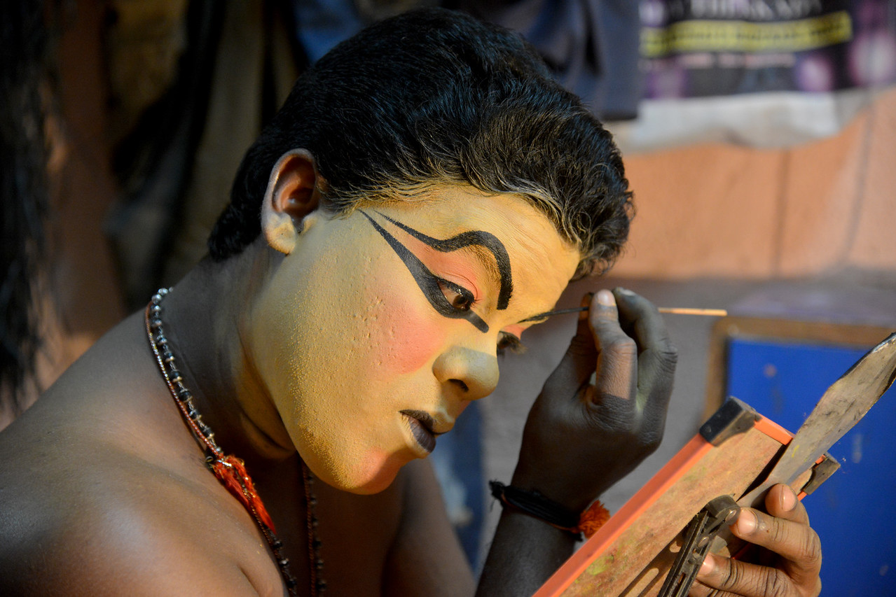Mr. Kalamandal Subin applies make up to dress up as Lalitha,the demon lady in a beautiful form of Nakkrathundi. Typically takes 3 to 4 hours to apply this make up.<br /> <br /> Mudra Kathakali Centre, Thekkady. Kathakali, literally meaning `story-play', is a dance-drama originated in the 17th century in Kerala, one of the smallest states in India lying on the west coast of the Indian peninsula. Kathakali is the result of a fusion between all Indian theater tradition represented by Koodiyattom and the indigenous tradition of folk dance forms. It was one of the Rajas (Chieftain) of Kottarakkara, who wrote the first play intended for Kathakali performance. They form a cycle of eight stories based on Ramayana. Stories typically deal with the Mahabharata, Ramayana and the ancient scriptures known as the Puranas. This is performed in a text which is generally Sanskritised Malayalam.<br /> <br /> Thekkady (Idukki district) in Kerala is the location of the Periyar National Park, which is an important tourist attraction in India.