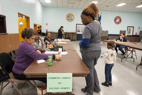 11/05/19 Wesley Bunnell | StaffrrVira Riley, L, assists Trena Edney at the check in table at the VFW 511 voting location early Tuesday afternoon. Edney is accompanied by her 4 year old daughter Sa'har Register.