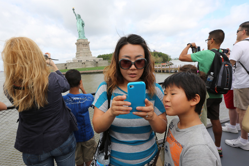 . Visitors to fhe Statue of Liberty take photos as they arrive on the first tourist ferry to leave Manhattan, Thursday, July 4, 2013 at  in New York. The Statue of Liberty finally reopened on the Fourth of July months after Superstorm Sandy swamped its little island in New York Harbor as Americans across the country marked the holiday with fireworks and barbecues. (AP Photo/Mary Altaffer)