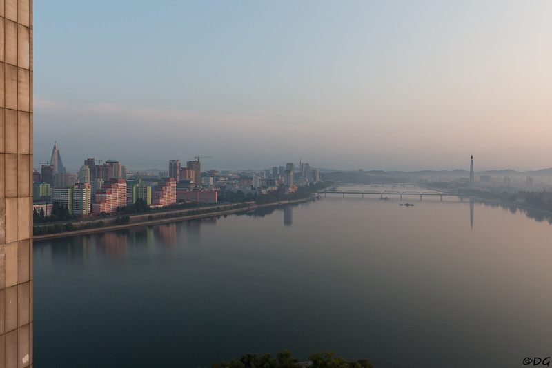 North Korea, Pyongyang. Early morning view from Yanggakdo Hotel. The pyramidal Ryugyong Hotel to the far left, the white Changjon Street complex of apartments to the left of Okryu Bridge and the Juche Tower to the right.