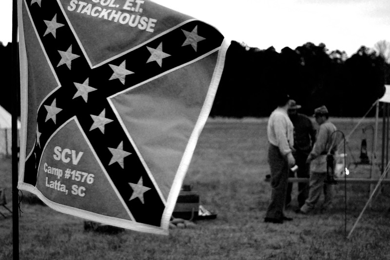 A flag for the Sons of Confederate Veterans flutters in the wind as the reenactors relax in their camp after dark. The Skirmish at Gamble's Hotel happened on March 5, 1885 when 500 federal soldiers, under the command of Reuben Williams of the 12th Indiana Infantry, marched into Florence to destroy the railroad depot but were met by Confederate soldiers backed up with 400 militia. The reenactment, held by the 23rd South Carolina Infantry, was held at the Rankin Plantation in Florence, South Carolina on Saturday, March 5, 2011. Photo Copyright 2011 Jason Barnette