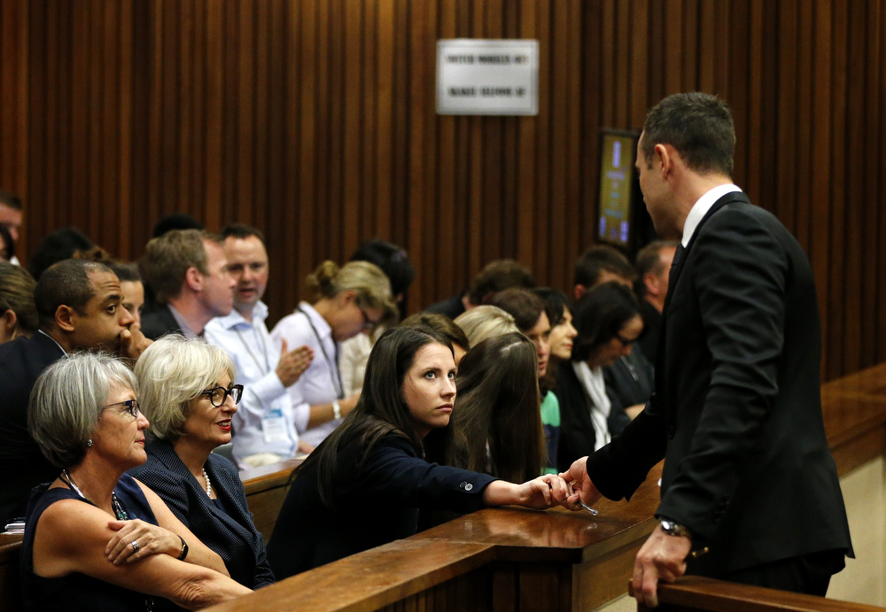 . Aimee Pistorius (C), sister of Olympic and Paralympic track star Oscar Pistorius (R) holds his hand ahead of his trial at the North Gauteng High Court in Pretoria, on March 5, 2014.  Oscar Pistorius\'s murder trial was set Wednesday to hear further testimony of screams and gunshots the night Reeva Steenkamp died, challenging the sprinter\'s defense against premeditated murder. (SIPHIWE SIBEKO/AFP/Getty Images)