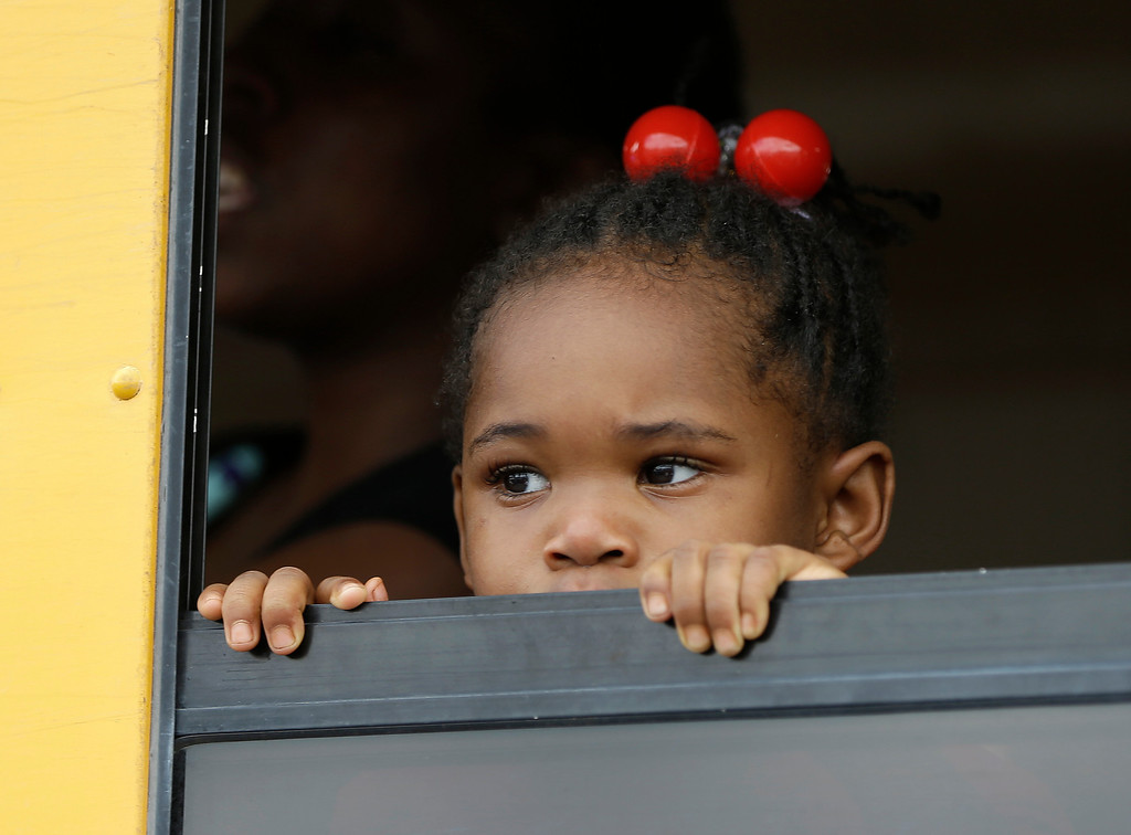 . A child peers out the window of a school bus as busses arrive with students after an incident at Ronald McNair Discovery Learning Academy, Tuesday, Aug. 20, 2013 in Decatur, Ga.  Superintendent Michael Thurmond says all students at Ronald E. McNair Discovery Learning Academy in Decatur east of Atlanta are accounted for and safe Tuesday and that he is not aware of any injuries. (AP Photo/John Bazemore)