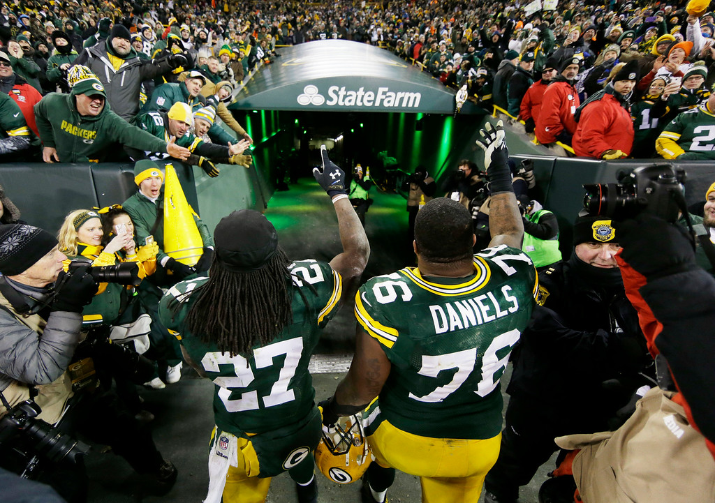 . Green Bay Packers\' Eddie Lacy (27) and Mike Daniels (76) celebrate after an NFL football game against the Detroit Lions Sunday, Dec. 28, 2014, in Green Bay, Wis. The Packers won 30-20. (AP Photo/Tom Lynn)
