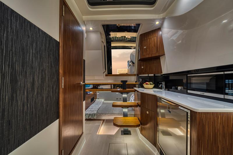 2021-Sundancer-370-Outboard-DAO370-cabin-access-door-mid-berth-bed-galley-microwave-refrigerator-04945.jpg