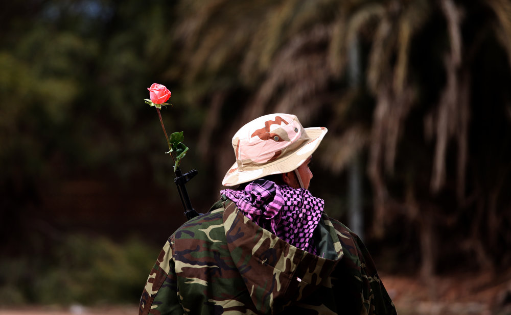 Description of . A member of Libya's security forces stands guard with a rose tucked in the barrel of his weapon in Benghazi, Libya, Saturday, Feb. 16, 2013, a day ahead of the two year anniversary of the uprising that ousted Moammar Gadhafi. (AP Photo/Mohammad Hannon)