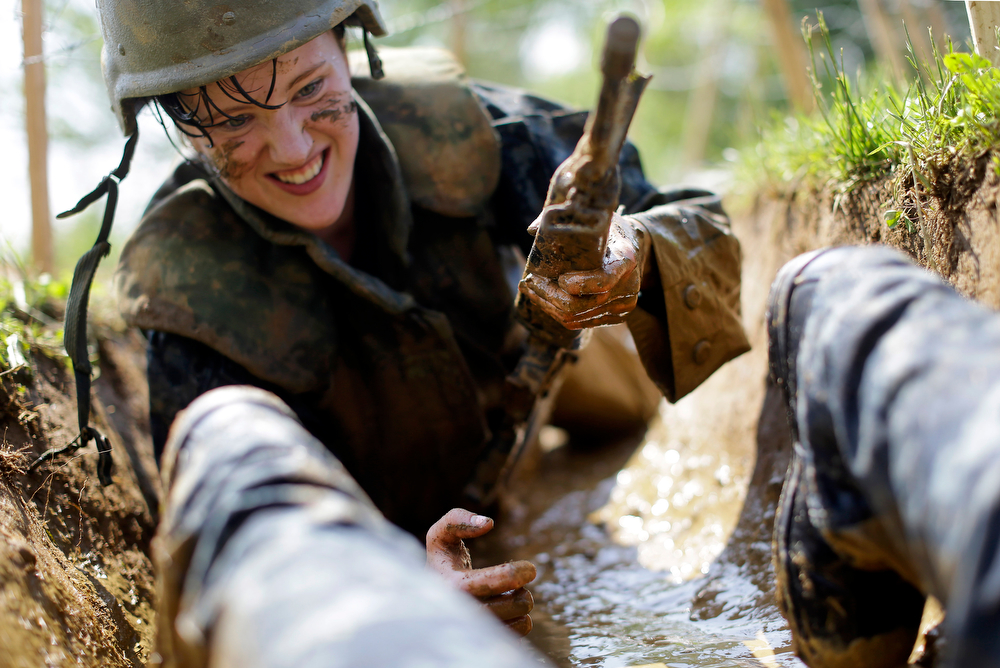 """. A freshman midshipman, known as a \""""plebe,\"""" crawls through a muddy trench underneath barbed wire during Sea Trials, a day of physical and mental challenges that caps off the freshman year at the U.S. Naval Academy in Annapolis, Md., Tuesday, May 13, 2014. (AP Photo/Patrick Semansky)"""