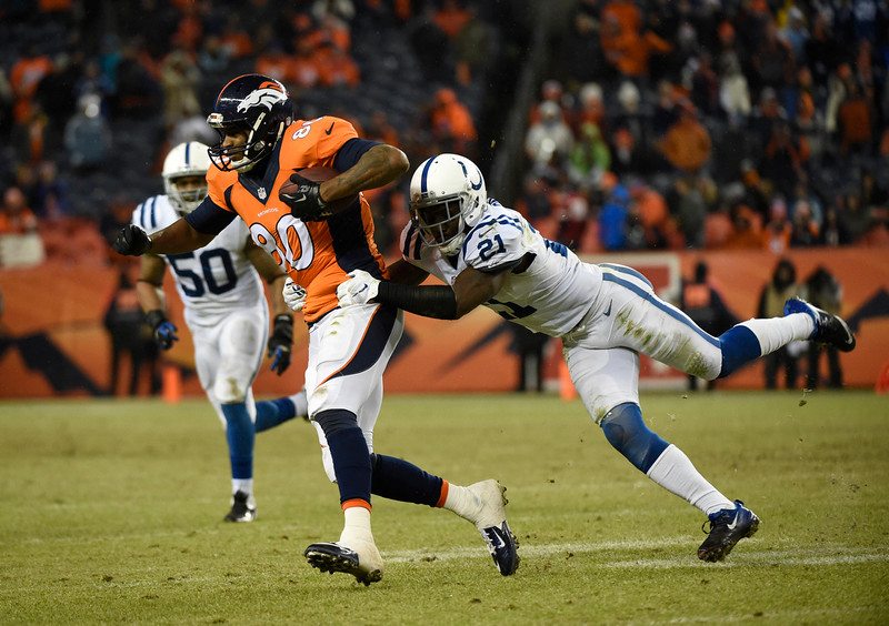 . Julius Thomas (80) of the Denver Broncos is tackled by Vontae Davis (21) of the Indianapolis Colts in the fourth quarter. The Denver Broncos played the Indianapolis Colts in an AFC divisional playoff game at Sports Authority Field at Mile High in Denver on January 11, 2015. (Photo by Joe Amon/The Denver Post)