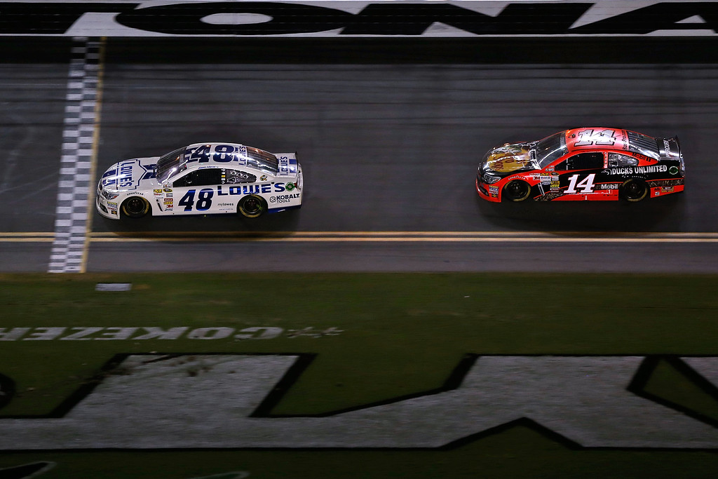 . DAYTONA BEACH, FL - JULY 06:  Jimmie Johnson, driver of the #48 Lowe\'s Dover White Chevrolet, crosses the start finish lne ahead of Tony Stewart, driver of the #14 Bass Pro Shops / Ducks Unlimited Chevrolet, to take the checkered fla and win the NASCAR Sprint Cup Series Coke Zero 400 at Daytona International Speedway on July 6, 2013 in Daytona Beach, Florida.  (Photo by Scott Halleran/Getty Images)