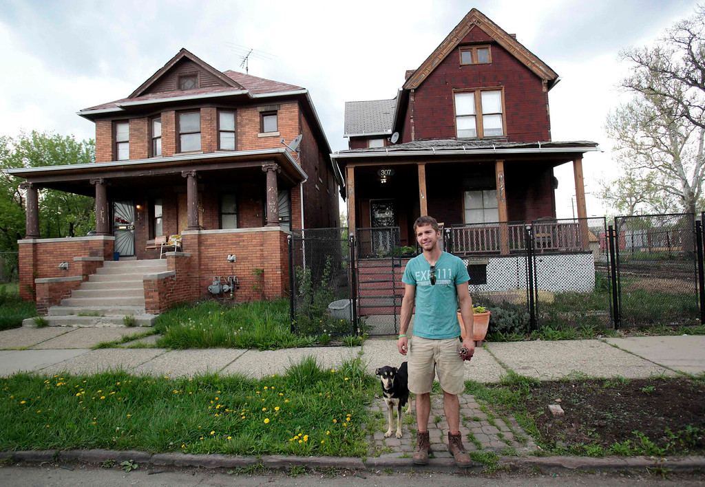 . Darin McLeskey, 22-years-old, stands with the stray dog he adopted in front of one of the properties he purchased at a Wayne County auction and plans on refurbishing in Detroit, Michigan May 9, 2013. Low property prices in Detroit in the wake of the housing crash in 2008 have lured investors from California to China. Speculators bank on high returns despite a financial crisis so dire Detroit\'s state-appointed emergency manager, Kevyn Orr, has cited a 50-50 chance the city will file for bankruptcy. Picture taken May 9, 2013.  REUTERS/ Rebecca Cook
