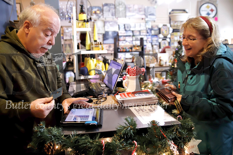 Sue Krysinski settles up with Stocking Stuffers Plus owner Gary Gilarno for a purchase on Small Business Saturday in Zelienople. Seb Foltz/Butler Eagle