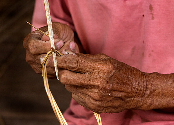 the hands of a basket weaver, weaving a basket.