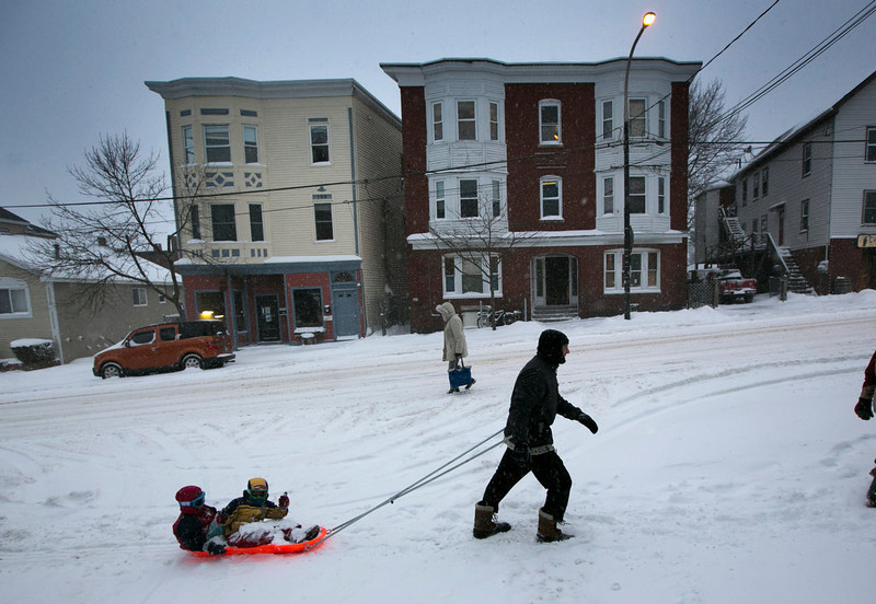 . Guy McChesney pulls Lucas McChesney and Nico Doyle on a sled up Munjoy Hill during a snow storm, Friday, Feb. 8, 2013, in Portland, Maine. Snow began falling across the Northeast on Friday, ushering in what was predicted to be a huge, possibly historic blizzard and sending residents scurrying to stock up on food and gas up their cars. The storm could dump 1 to 3 feet of snow from New York City to Boston and beyond. (AP Photo/Robert F. Bukaty)
