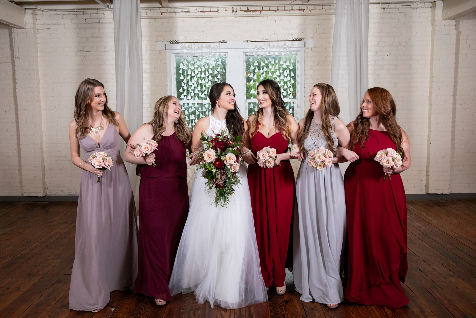 five bridesmaids locking arms while they smile and look toward the bride in the middle
