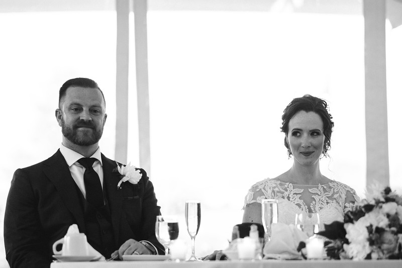 The bride and groom sit smiling at their table.