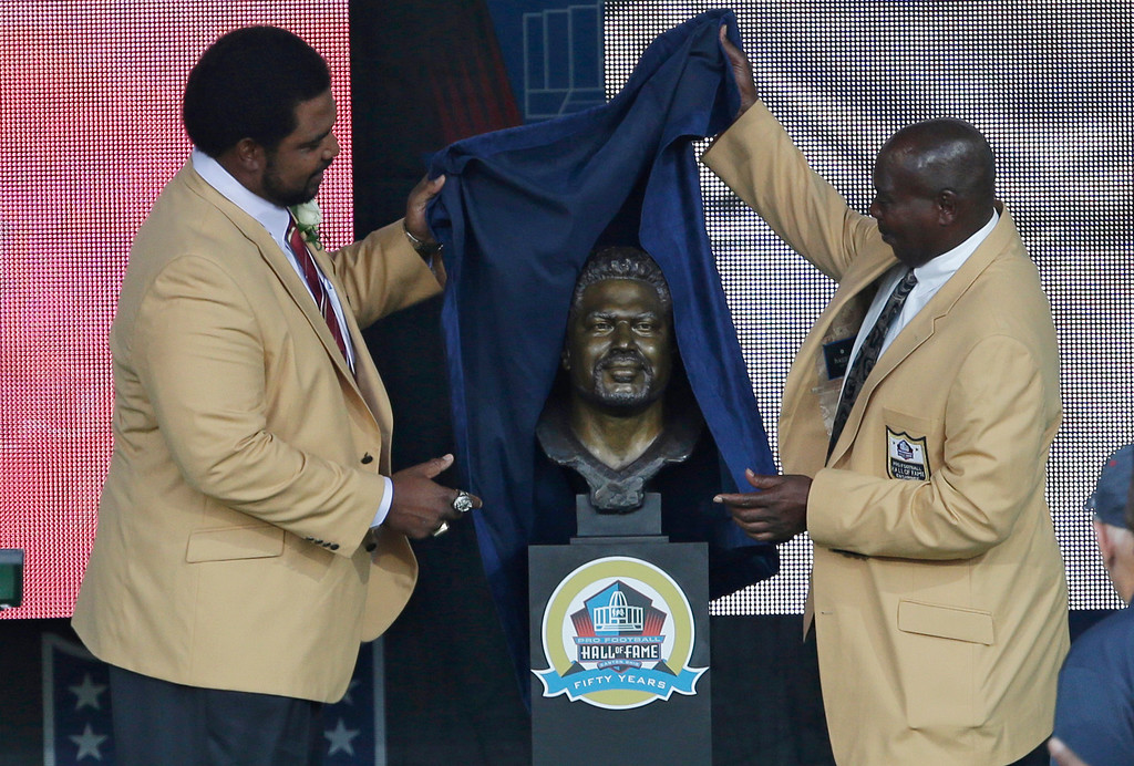 . Former NFL football player Jonathan Ogden, left, and his presenter, Baltimore Ravens General Manager Ozzie Newsome, unveil the bust during the induction ceremony at the Pro Football Hall of Fame Saturday Aug. 3, 2013, in Canton, Ohio. (AP Photo/Tony Dejak)