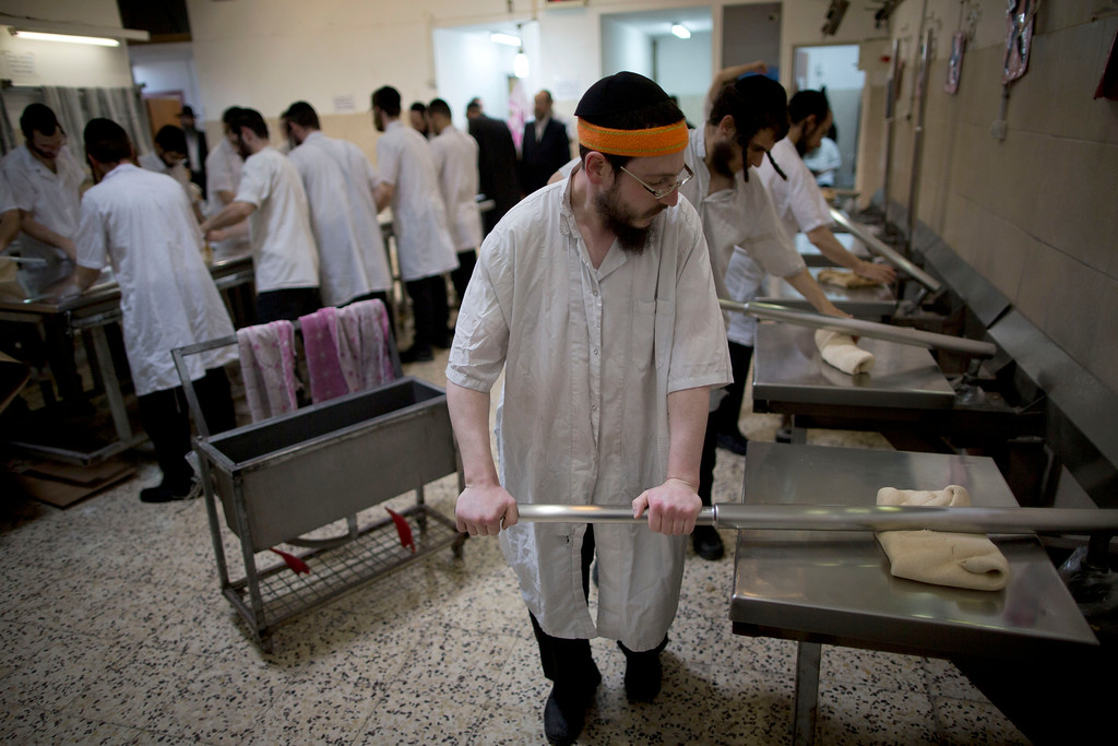 . Ultra-Orthodox Jews prepare special matzoh, a traditional handmade Passover unleavened bread, at a bakery in Bnei Brak, Israel. Wednesday, April 20, 2016. Jews are forbidden to eat leavened foodstuffs during the Passover holiday that celebrates the biblical story of the Israelites\' escape from slavery and exodus from Egypt. (AP Photo/Oded Balilty)