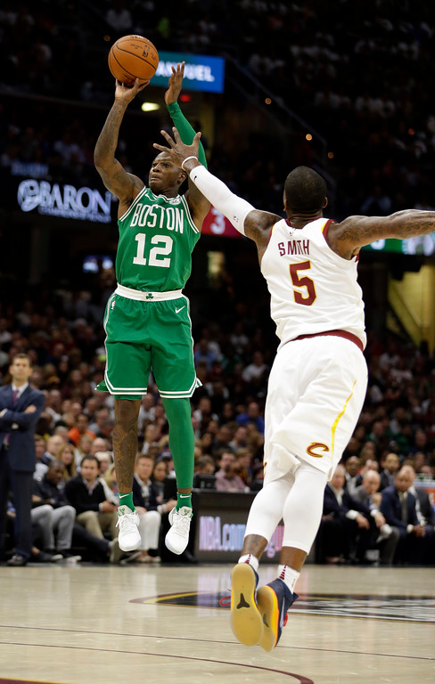 . Boston Celtics\' Terry Rozier (12) shoots over Cleveland Cavaliers\' JR Smith (5) in the first half of an NBA basketball game, Tuesday, Oct. 17, 2017, in Cleveland. (AP Photo/Tony Dejak)