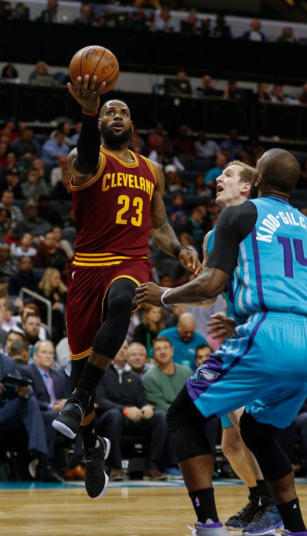 . Cleveland Cavaliers forward LeBron James, left, drives to the basket past Charlotte Hornets center Cody Zeller and forward Michael Kidd-Gilchrist in the second half of an NBA basketball game in Charlotte, N.C., Saturday, Dec. 31, 2016. Cleveland won 121-109. (AP Photo/Nell Redmond)