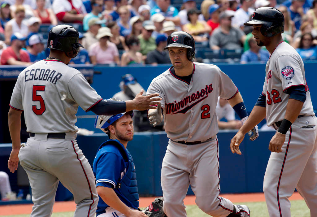 . Toronto Blue Jays catcher Josh Thole watches as Minnesota Twins\' Brian Dozier (2) is congratulated by teammates Eduardo Escobar (5) and Aaron Hicks (32) after scoring them on his three-run home run during the seventh inning. (AP Photo/The Canadian Press, Frank Gunn)