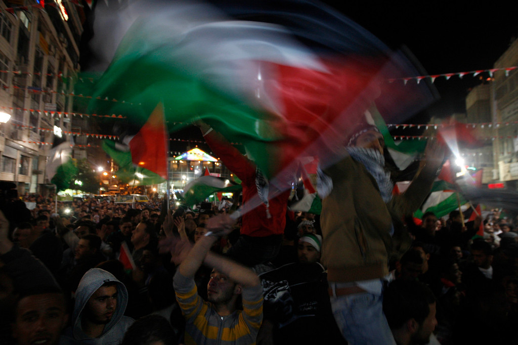 . Palestinians wave palestinian flags as they watch the U.N. General Assembly votes on a resolution to upgrade the status of the Palestinian Authority to a nonmember observer state, In the west bank city of Ramallah, Thursday, Nov. 29, 2012.  The U.N. General Assembly has voted by a more than two-thirds majority to recognize the state of Palestine. The resolution upgrading the Palestinians\' status to a nonmember observer state at the United Nations was approved by the 193-member world body late Thursday by a vote of 138-9 with 41 abstentions. (AP Photo/Majdi Mohammed)