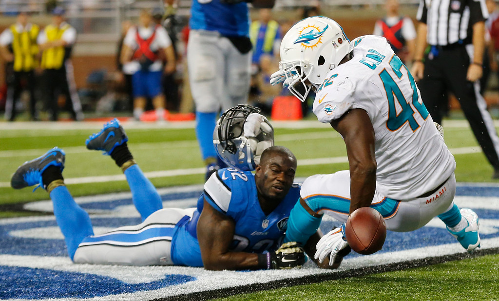 . Detroit Lions defensive end Darryl Tapp (52) loses his helmet after deflecting a pass intended for Miami Dolphins tight end Charles Clay (42) during the second half of an NFL football game in Detroit, Sunday, Nov. 9, 2014. (AP Photo/Paul Sancya)