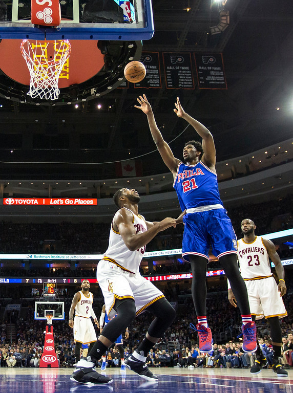 . Philadelphia 76ers\' Joel Embiid, center, puts up the shot with Cleveland Cavaliers\' Tristan Thompson, left, defending during the first half of an NBA basketball game, Saturday, Nov. 5, 2016, in Philadelphia. (AP Photo/Chris Szagola)