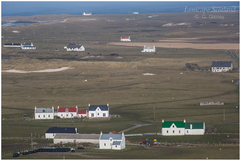 Houses in a flat landscape - Balevullin and Cornaig from Beinn Hough