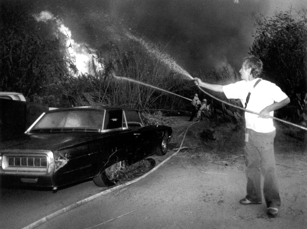 . A man uses a garden hose to wet vegetation near his house at Pacific Coast  Highway and Topanga Canyon Boulevard on November 3, 1993.   Los Angeles Daily News file photo