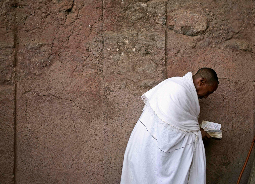 . An Orthodox Christian prays outside of a famous monolithic rock-cut church during a Good Friday celebration in Lalibela, May 3, 2013.   REUTERS/Goran Tomasevic