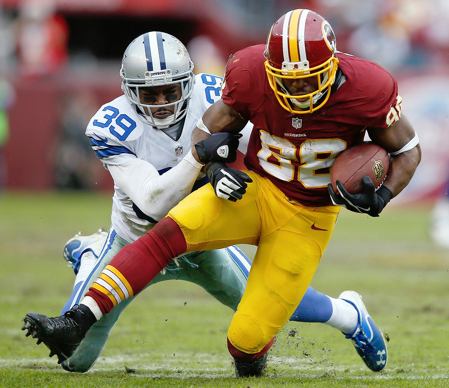 . Washington Redskins wide receiver Pierre Garcon is hauled to the turf by Dallas Cowboys cornerback Brandon Carr during the second half of an NFL football game in Landover, Md., Sunday, Dec. 22, 2013. (AP Photo/Evan Vucci)