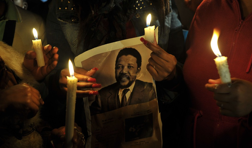 """. A group of well-wishers hold candles and a photo of Nelson Mandela as they pray for his recovery outside the Mediclinic heart hospital where he is hospitalized in Pretoria on June 27, 2013. A critically ill Nelson Mandela showed tentative signs of improvement on June 27 as South Africa-bound US President Barack Obama led a chorus of support for the \""""hero for the world\"""". South African President Jacob Zuma, who had abruptly cancelled a trip abroad to be near the 94-year-old anti-apartheid icon, reported he \""""remains critical but is now stable\"""". ALEXANDER JOE/AFP/Getty Images"""