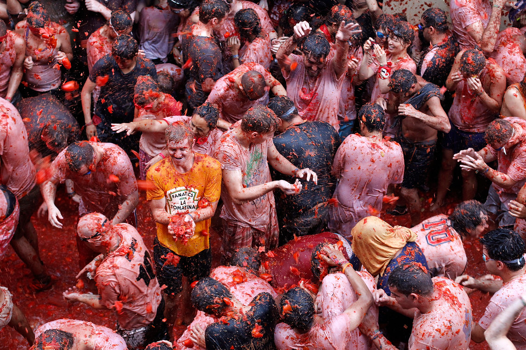""". People throw tomatoes at each other during the annual \""""tomatina\"""" tomato fight fiesta in the village of Bunol, 50 kilometers outside Valencia, Spain, Wednesday, Aug. 28, 2013. Thousands of people are splattering each other with tons of tomatoes in the annual \""""Tomatina\"""" battle in recession-hit Spain, with the debt-burdened town charging participants entry fees this year for the first time. Bunol town says some 20,000 people are taking part in Wednesday\'s hour-long street bash, inspired by a food fight among kids back in 1945. Participants were this year charged some euro10 ($13) to foot the cost of the festival. Residents do not pay. (AP Photo/Alberto Saiz)"""