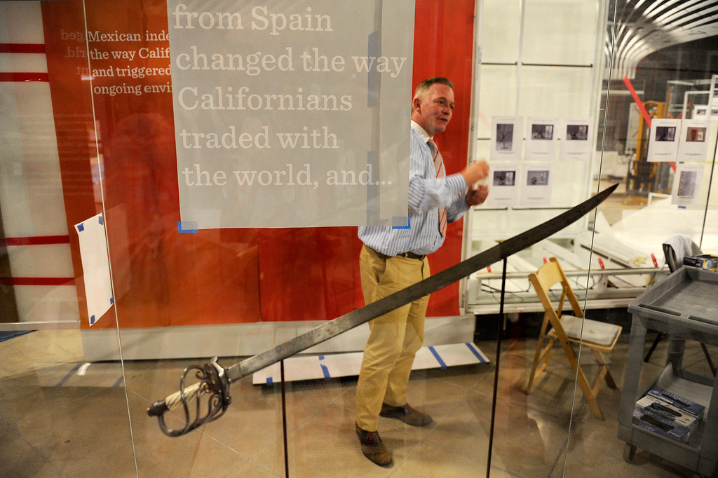 """. Simon Adlam, director of exhibits and creative director, stands by a saber at the \""""Becoming Los Angeles\"""" exhibit set to open at the Natural History Museum of Los Angeles County, Tuesday, April 2, 2013. (Michael Owen Baker/Staff Photographer)"""
