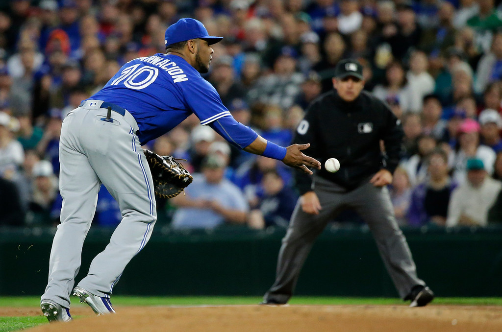 . Toronto Blue Jays first baseman Edwin Encarnacion underhands the ball to starting pitcher J.A. Happ (not shown) to get Seattle Mariners\' Robinson Cano out at first in the first inning of a baseball game, Tuesday, Sept. 20, 2016, in Seattle. (AP Photo/Ted S. Warren)