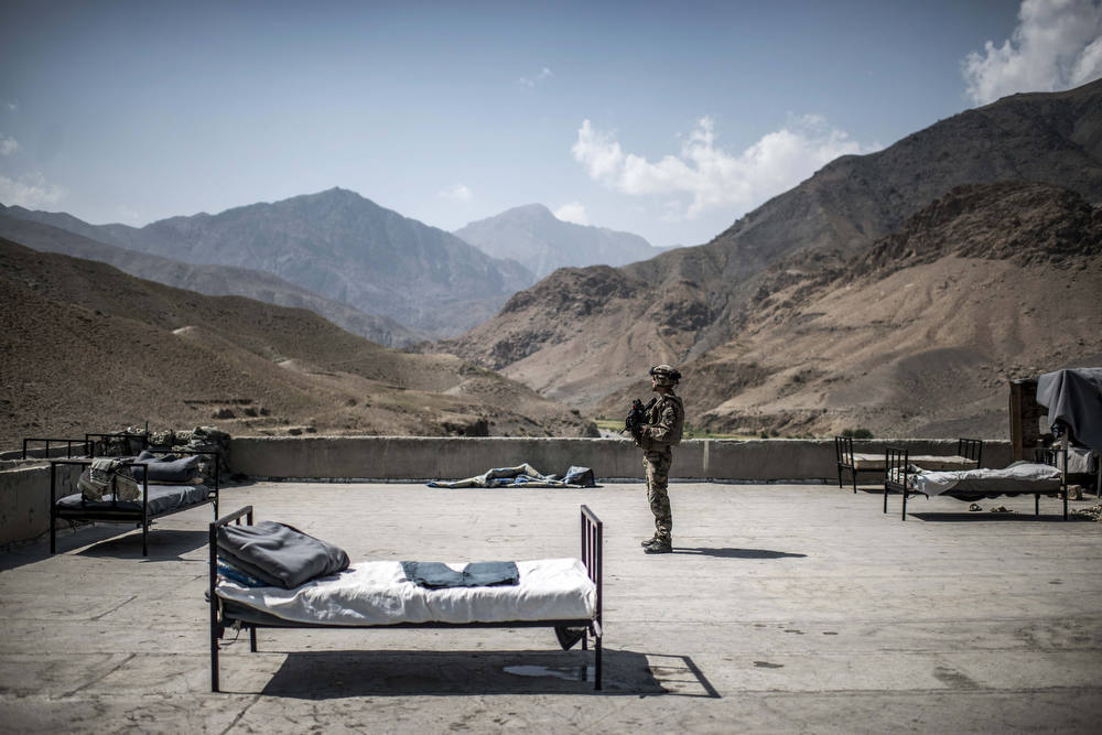 Description of . A French soldier stands on a rooftop of an Afghan National Police (ANP) combat post on September 24, 2012, in a village on the road to Naghlu the French army base. Beds are used by the policemen to sleep outside due to the heat. France is the fifth largest contributor to NATO's International Security Assistance Force (ISAF), which is due to pull out the vast majority of its 130,000 troops by the end of 2014. AFP PHOTO / JEFF  PACHOUD/AFP/Getty Images