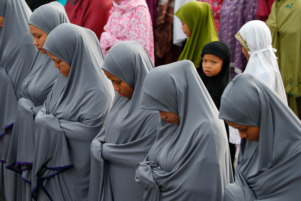 . A family of Filipino Muslims, garbed in identical dresses, pray to celebrate the end of the holy month of Ramadan known as Eid al-Fitr Friday, June 15, 2018 at the Blue Mosque in suburban Taguig city, east of Manila, Philippines. Muslims all over the world mark Eid al-Fitr with prayers, family reunions and gift-givings. (AP Photo/Bullit Marquez)