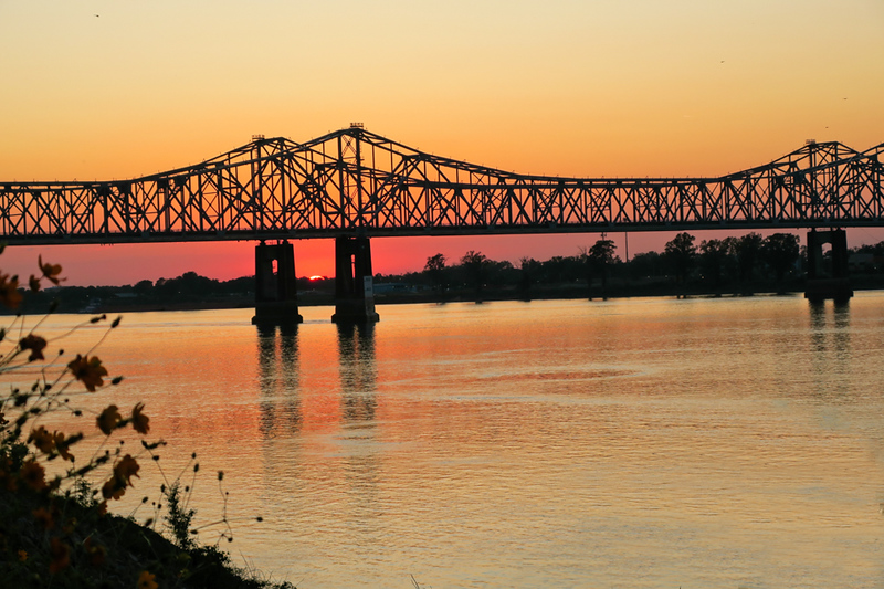 Sunset shines through a bridge over the Mississippi River in Natchez.