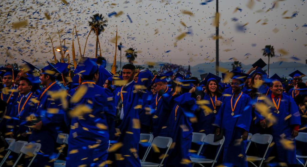 . Blue and yellow confetti flies through the air on new graduates, at John H Francis Polytechnic High School, Sun Valley, Calif., June 7, 2013. Photo: Lynn Levitt.