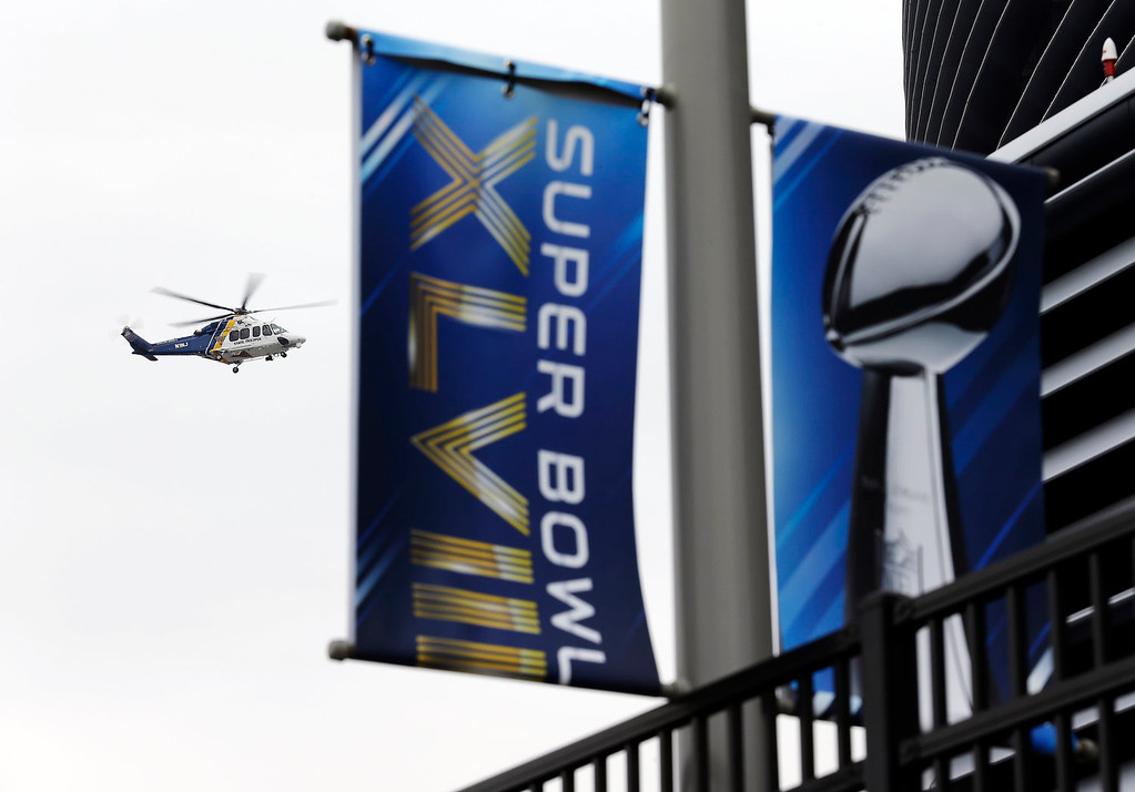 . A police helicopter flies over MetLife Stadium  before the NFL Super Bowl XLVIII football game between the Seattle Seahawks and the Denver Broncos Sunday, Feb. 2, 2014, in East Rutherford, N.J. (AP Photo/Ted S. Warren)