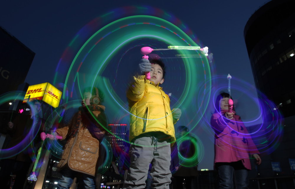 Description of . South Korean children spin illuminated sticks during 'Cyber Jwibulnoli' at Everland on February 21, 2013 in Seoul, South Korea. Jwibulnoli is originally played on the first full moon of the lunar year, that is February 25 this year.  (Photo by Chung Sung-Jun/Getty Images)