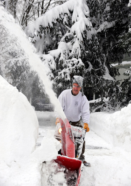 . Kurt Almond uses a snowblower to clear his driveway so his wife can attend to her Pharmacy job in East Aurora, , N.Y. Thursday, Nov. 20, 2014.  A new blast of lake-effect snow pounded Buffalo for a third day piling more misery on a city already buried by an epic, deadly snowfall that could leave some areas with nearly 8 feet of snow on the ground when it\'s all done. (AP Photo/Gary Wiepert)